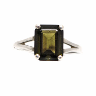 An emerald cut moldavite cabochon set into a simple sterling silver ring against a white background