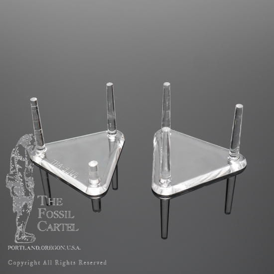 A pair of acrylic triangle peg stands against a black background