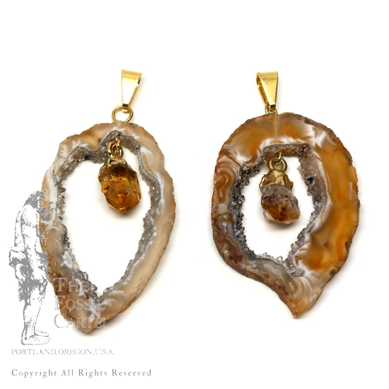 Agate geode slice pendants with citrine crystals linked in the middle featuring gold plated bails against a white background