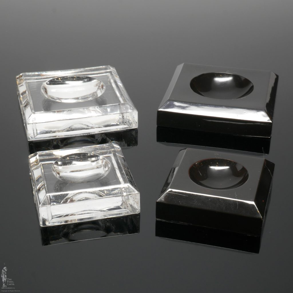 Clear and black square dimple block acrylic stands against a black background