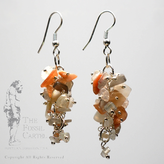 A pair of mixed moonstone chip dangle earrings in a grape style cluster against a grey background