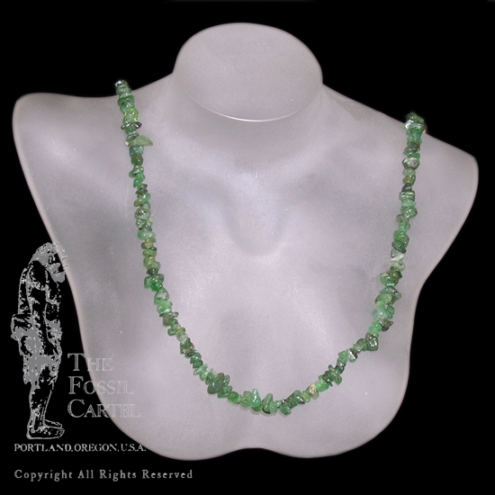 A tumbled emerald chip necklace against a black background