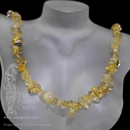 A rutilated quartz chip necklace against a black background
