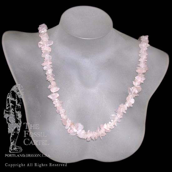 A tumbled rose quartz chip necklace against a black background