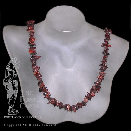 A tumbled red tiger's eye chip necklace against a black background