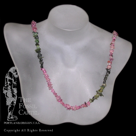 A pink and green tourmaline chip necklace against a black background
