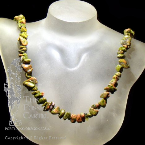 A tumbled unakite chip necklace against a black background