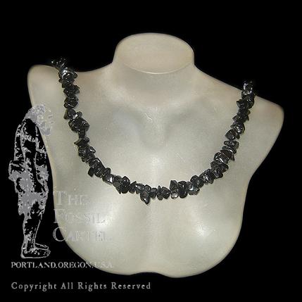 A black tourmaline chip necklace against a black background