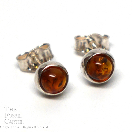 A pair of simple round sterling silver stud earrings with amber cabochons against a white background