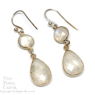 A pair of sterling silver earrings featuring a round faceted rainbow moonstone at the top of the earring with a teardrop faceted moonstone linked at the base against a white background