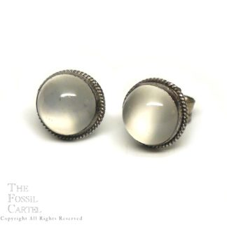 A pair of round sterling silver stud earrings featuring round colorless moonstone cabochons against a white background