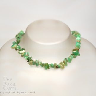 A tumbled chrysoprase chip necklace against a grey background