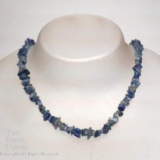 A tumbled kyanite chip necklace against a grey background