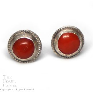 A pair of round red coral stud earrings with a roped bezel in sterling silver against a white background