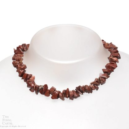 A necklace made of red tumbled brecciated jasper chips against a grey background