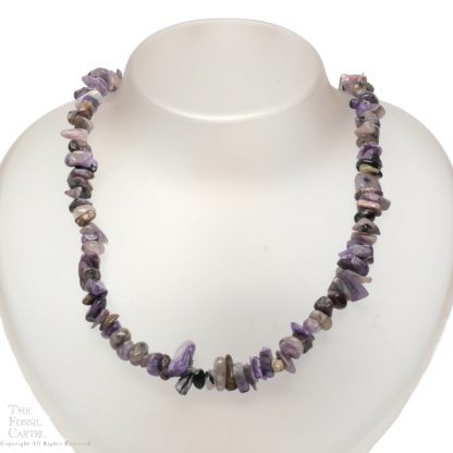 A necklace made of tumbled charoite chips against a white background