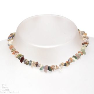 A necklace made of mixed stone chips against a grey background