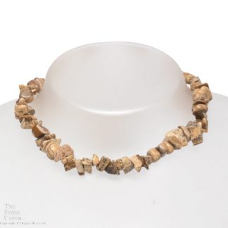 A necklace made of picture jasper chips against a grey background