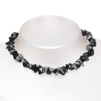 A stone chip necklace made of snowflake obsidian against a grey background