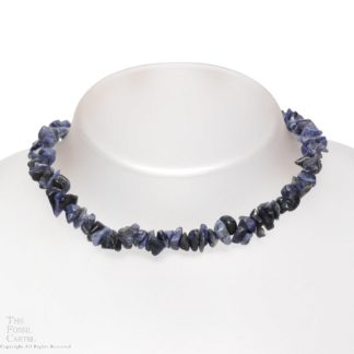 A stone chip necklace made of sodalite against a grey background