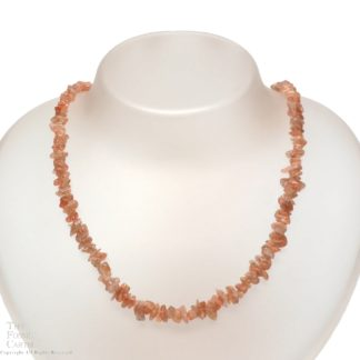 A necklace made of indian sunstone chips against a white background