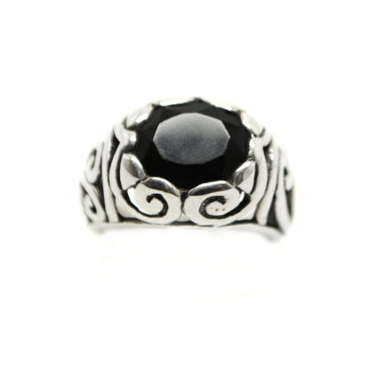 A piece of jet black onyx oval faceted and set in an intricately carved-out sterling silver ring against a white background