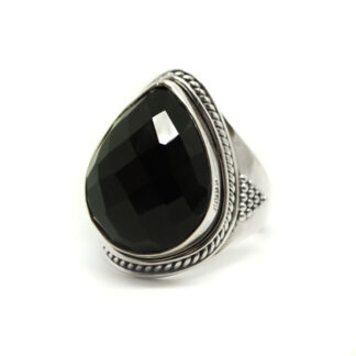 Jet black onyx cut into a faceted teardrop shape set in a sterling silver ring with roping around the bezel set against a white background