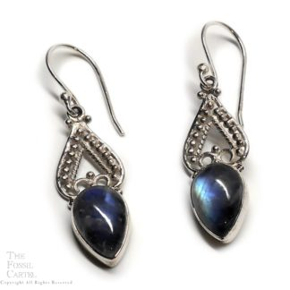 A pair of ornate sterling silver earrings featuring teardrop rainbow moonstone cabochons against a white background