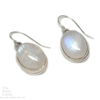 A pair of simple sterling silver earrings with oval rainbow moonstone cabochons against a white background