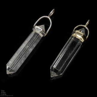 Two clear quartz crystal shaped pendants in sterling silver or gold plated against a black background
