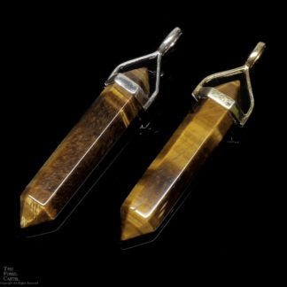 Two simple crystal shaped tiger's eye pendants set in sterling silver and gold plated against a black background