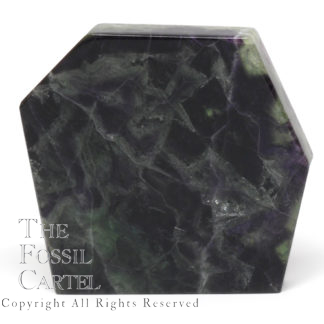 A slab of translucent rainbow fluorite cut and polished on all sides, against a white background