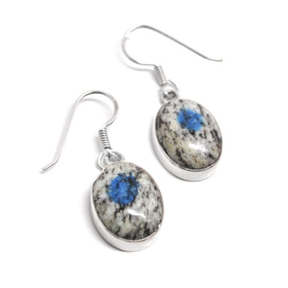 A pair of daingly sterling silver earrings set with oval K2 granite cabochons against a white background