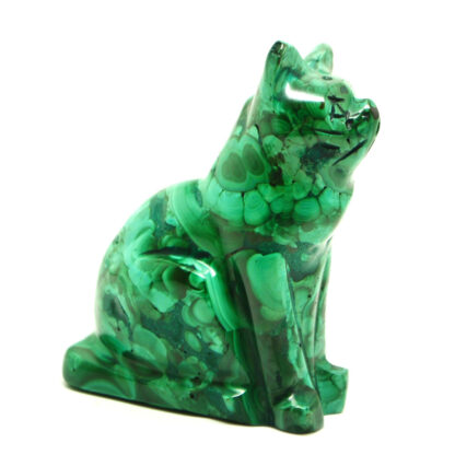 A piece of malachite carved and polished into a cat figurine against a white background