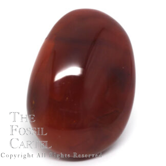 A deep orange carnelian palm stone against a white background
