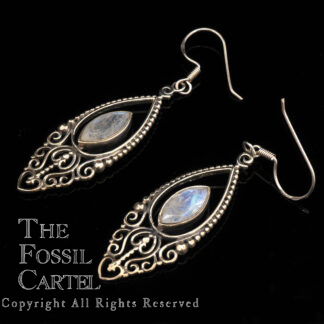 A pair of ornate sterling silver earrings feautring faceted diamond shaped rainbow moonstones against a black background