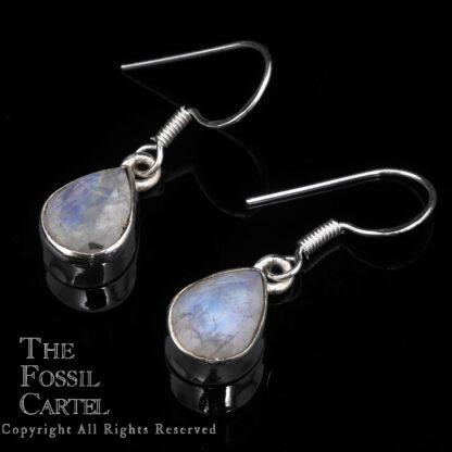 A pair of sterling silver rainbow moonstone teardrop dangle earrings against a black background