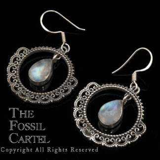 A pair of ornate sterling silver earrings featuring teardrop rainbow moonstone cabochons against a black background
