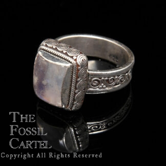 A sterling silver ring with an ornate bezel and band featuring a square rainbow moonstone against a black background