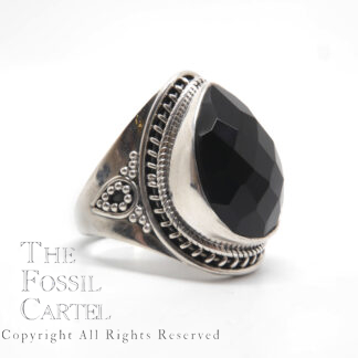 Jet black onyx cut into a faceted teardrop cabochon set in a sterling silver ring with roping around the bezel set against a white background