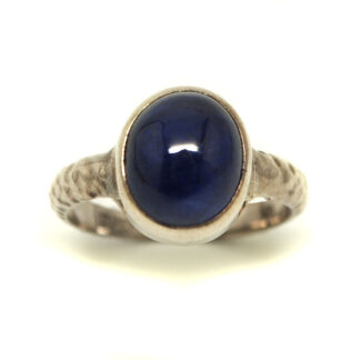 Translucent Sapphire cabochon set in sterling silver ring with hammered style band against a white background