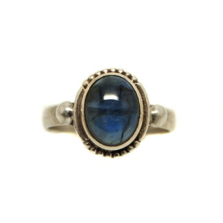 Translucent Sapphire cabochon set in sterling silver ring with intricate bezel and slim band against a white background