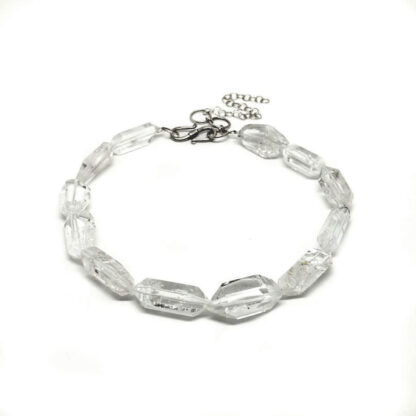 A beaded necklace of double terminated clear quartz crystal against a white background