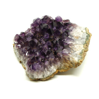 A side view of a purple amethyst crystal cluster with agate banding along the edges of the cluster against a white background