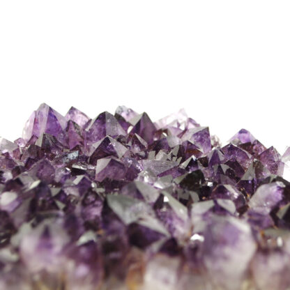 A purple amethyst crystal cluster against a white background