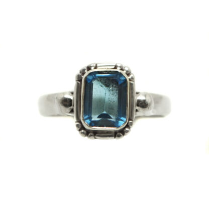 A blue topaz gemstone faceted into a rectangle shape and set in a decorative sterling silver ring against a white background