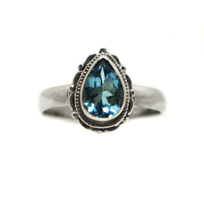 A blue topaz gemstone faceted into a teardrop shape and set in an intricate sterling silver ring against a white background