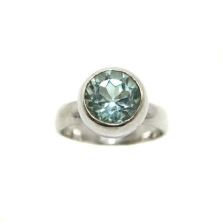 A round blue topaz faceted gemstone set into a sterling silver ring against a white background