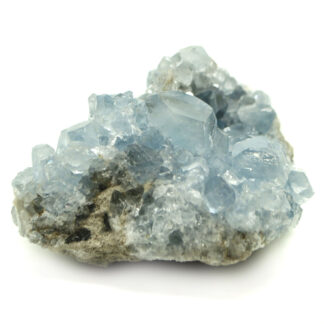 A gemmy blue celestite crystal cluster with well defined crystals against a white background