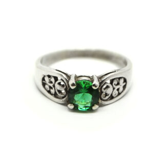 A round faceted emerald obsidianite gemstone prong-set into a filigree sterling silver ring against a white background